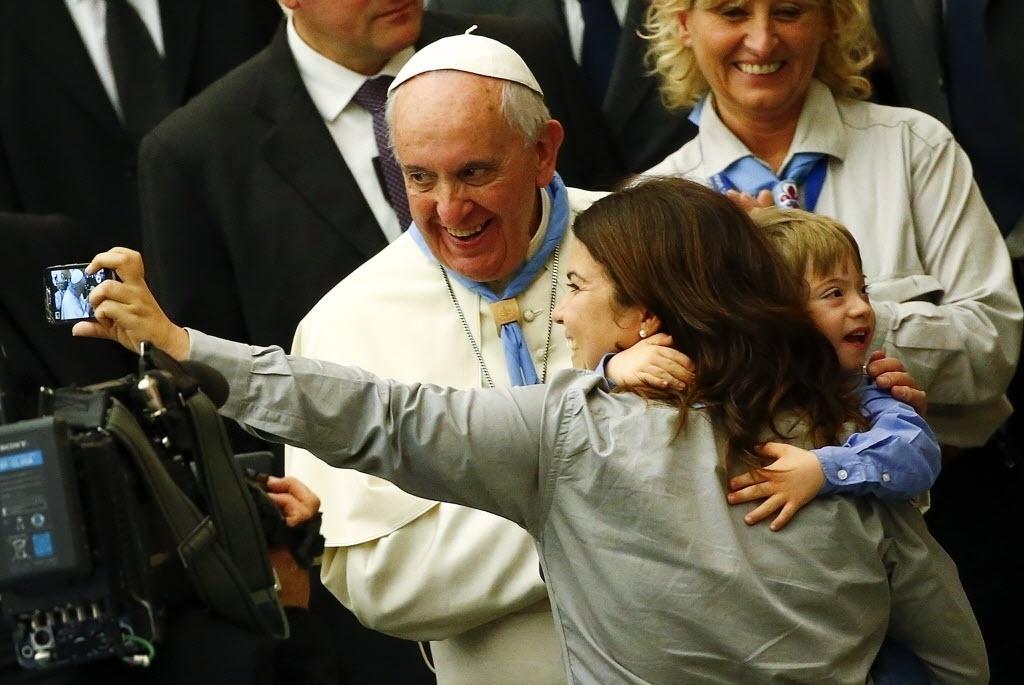 8.nov.2014 - Papa Francisco posa para selfie de uma fiel durante uma audiência especial com escoteiros adultos na sala Paulo 6º, no Vaticano