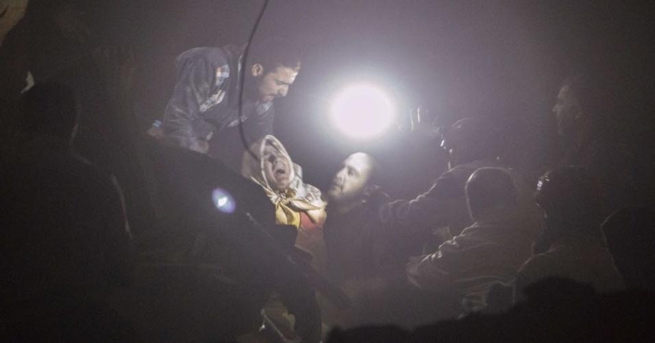 12.nov.2014 - Mulher se desespera enquanto é resgatada de um prédio em chamas após um ataque aéreo das forças do governo no bairro de Kalasa, na cidade síria de Aleppo, nesta quarta-feira (12). No início da semana, o ditador sírio, Bashar Assad, disse que estava pronto para estudar o plano da ONU para