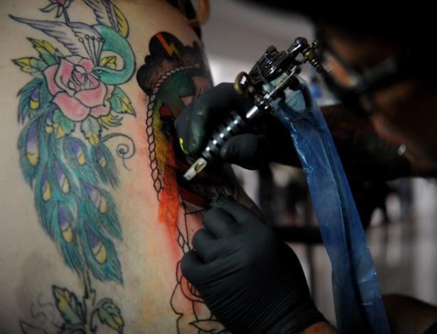 Tatuador trabalha em uma cliente: cuidados com agulha e pigmentação
