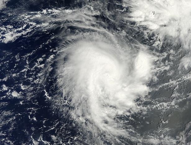"""18.nov.2014 - Satélite da Nasa captura uma imagem do oceano Índico, perto da ilha Diego Garcia (território britânico), no momento da passagem do ciclone tropical Adjali. A imagem mostra uma concentração de fortes tempestades em torno do centro da circulação e diversas tempestades que se estendem do centro ao sul, parecendo uma """"cauda"""". Os ventos máximos do ciclone estavam perto de 110 km/h"""
