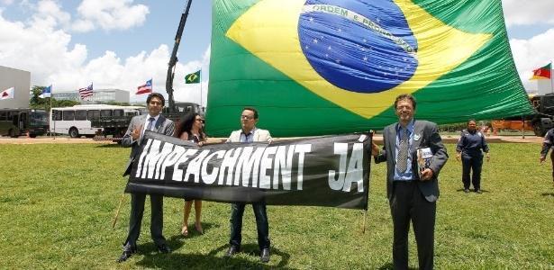 19.nov.2014 - Manifestantes protestaram nesta quarta-feira (19) pelo impeachment da presidente Dilma Rousseff durante cerimônia para comemorar o dia da Bandeira, realizada no gramado em frente ao Congresso Nacional, em Brasília, com uma bandeira nacional gigante