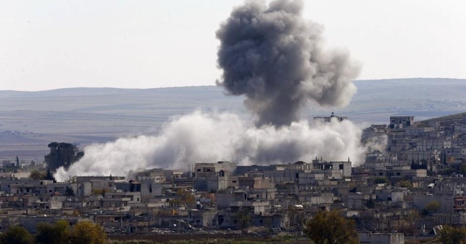 23.nov.2014 - Nuvem de fumaça toma conta do céu da cidade síria de Kobani, próxima da fronteira entre a Síria e a Turquia, neste domingo (23). Combatentes do grupo extremista EI (Estado Islâmico) tentam tomar controle da cidade há mais de dois meses
