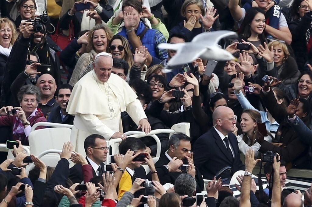 23.nov.2014 - Pomba passa sobre multidão no momento em que o papa Francisco chega à praça São Pedro para cerimônia de canonização de seis novos santos homens e uma santa mulher