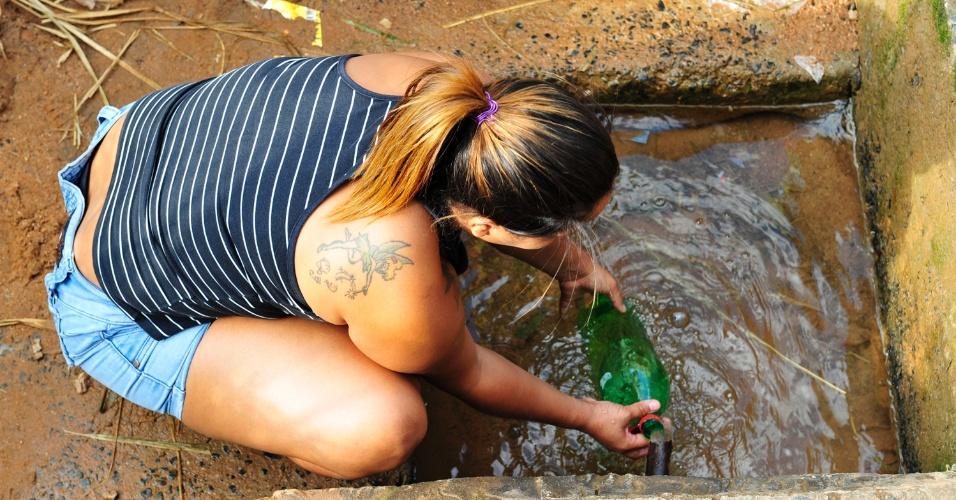 3.dez.2014 - Moradora de Campinas pega água de bica em Itupeva (SP) devido à seca. Laudo da Sanasa, empresa responsável pelo abastecimento de água e saneamento de Campinas, informou que a água é imprópria para consumo, mesmo assim muitas pessoas continuam a pegar água no local