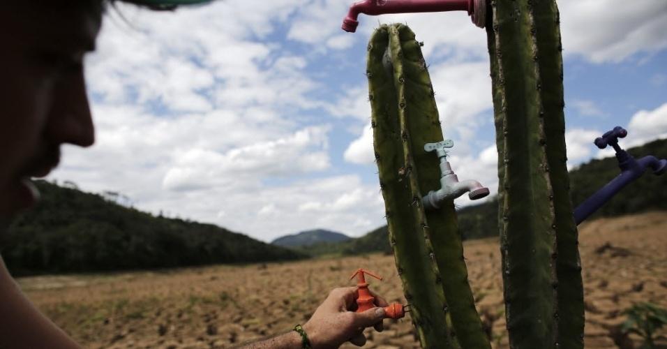 """3.dez.2014 - O artista e ativista Mundano """"planta"""" um cacto com torneiras acopladas no leito seco da represa de Atibainha, que faz parte do Sistema Cantareira, em Nazaré Paulista"""