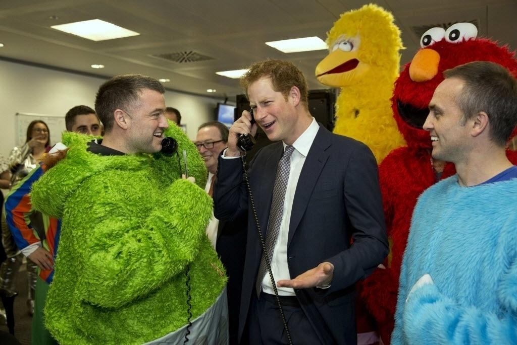 3.dez.2014 - O príncipe Harry (ao centro) do Reino Unido encontrou-se nesta quarta-feira (3) com voluntários vestidos como os personagens do seriado Vila Sésamo durante um evento de caridade, no centro de Londres, na Inglaterra