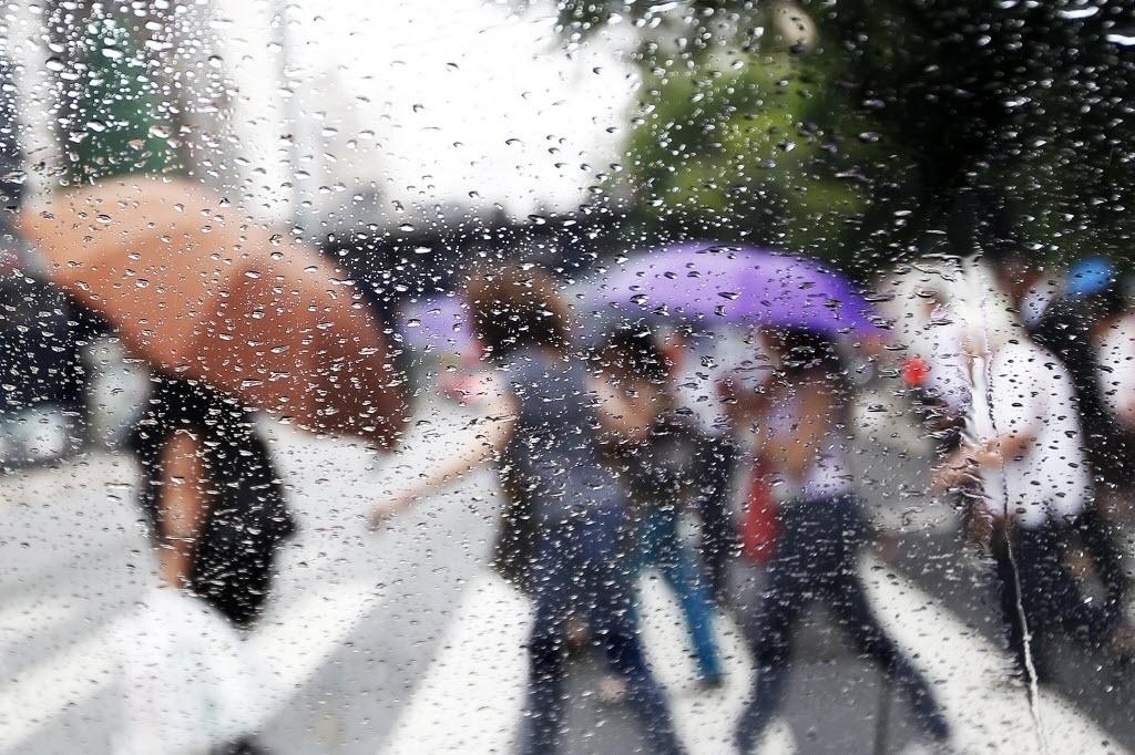 4.dez.2014 - Paulistanos atravessaram a avenida Paulista, em São Paulo, se protegendo da garoa desta quinta-feira (4). A chuva pode ajudar a encher os reservatórios de água que atendem a capital. Como não choveu entre esta terça-feira (2) e quarta-feira (3), os níveis dos mananciais caiu mais uma vez. O do Sistema Cantareira, que fornece água para 6,5 milhões de pessoas, passou de 8,5% para 8,4%, enquanto o do Alto Tietê, que abastece 4,5 milhões de pessoas, caiu de 5,5% para 5,4%