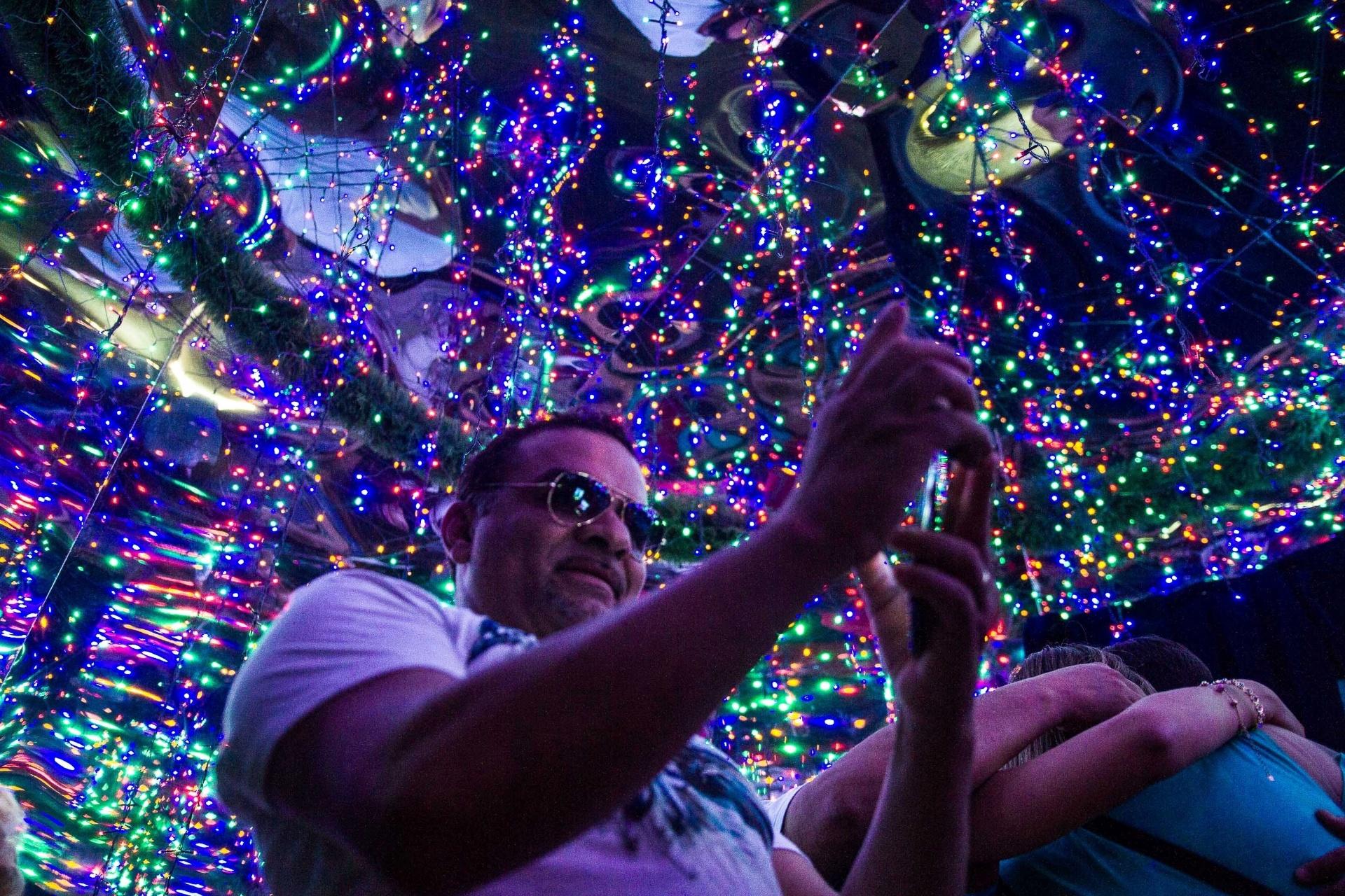 7.dez.2014 - Visitantes fazem selfies dentro do prisma montado por agência bancária tradicionalmente conhecida pela sua decoração de natal, na avenida Paulista, em São Paulo, neste domingo (7)