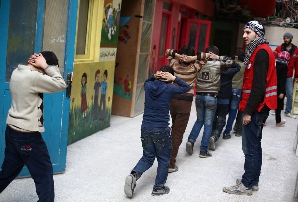 11.dez.2014 - Crianças sírias participam de treinamento de evacuação de escola promovido Crescente Vermelho Árabe , em Douma, na Síria.