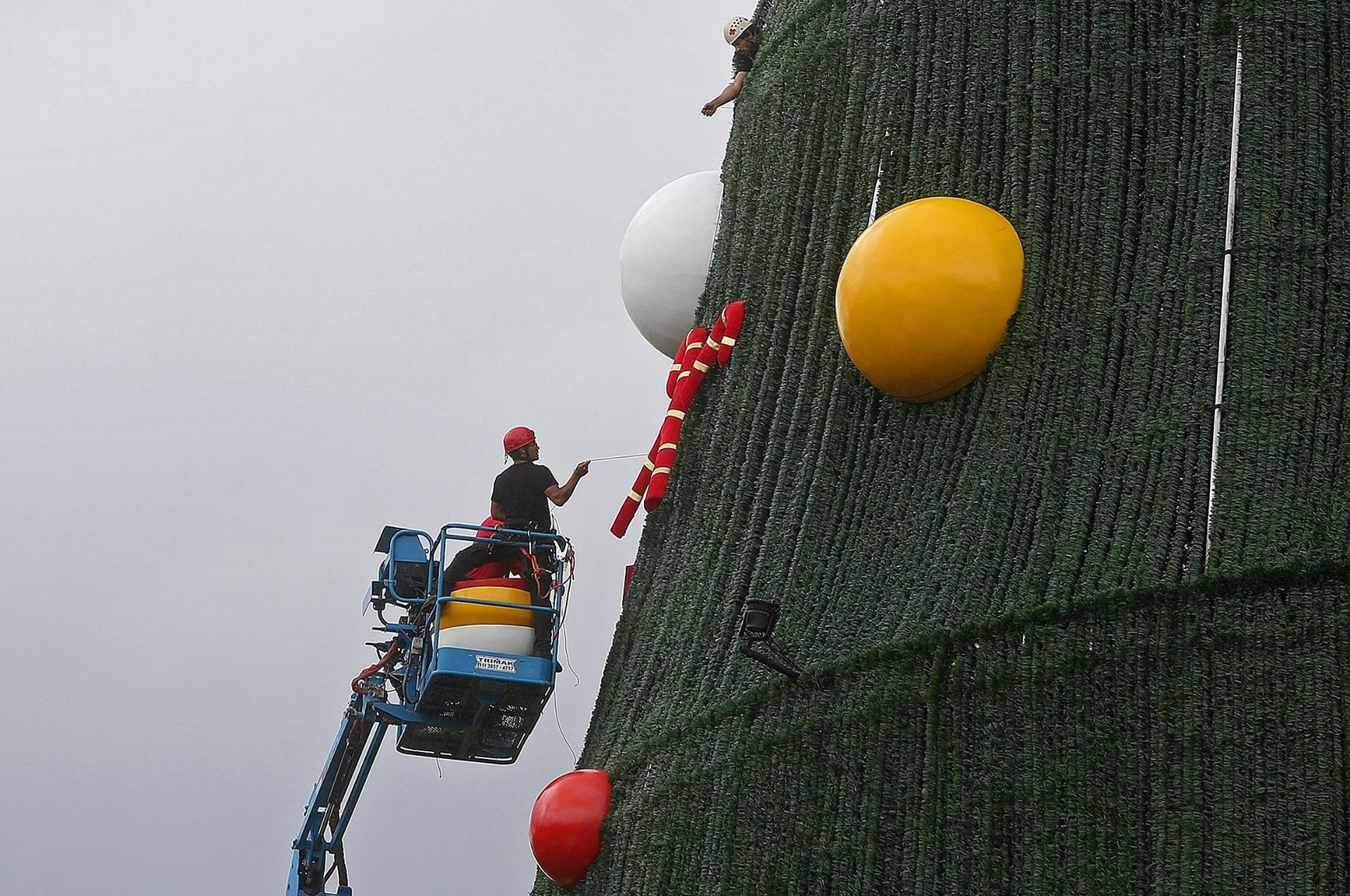 11.dez.2014 - Trabalhadores instalam uma árvore de Natal gigante na cidade de São Paulo, nesta quinta-feira (11)