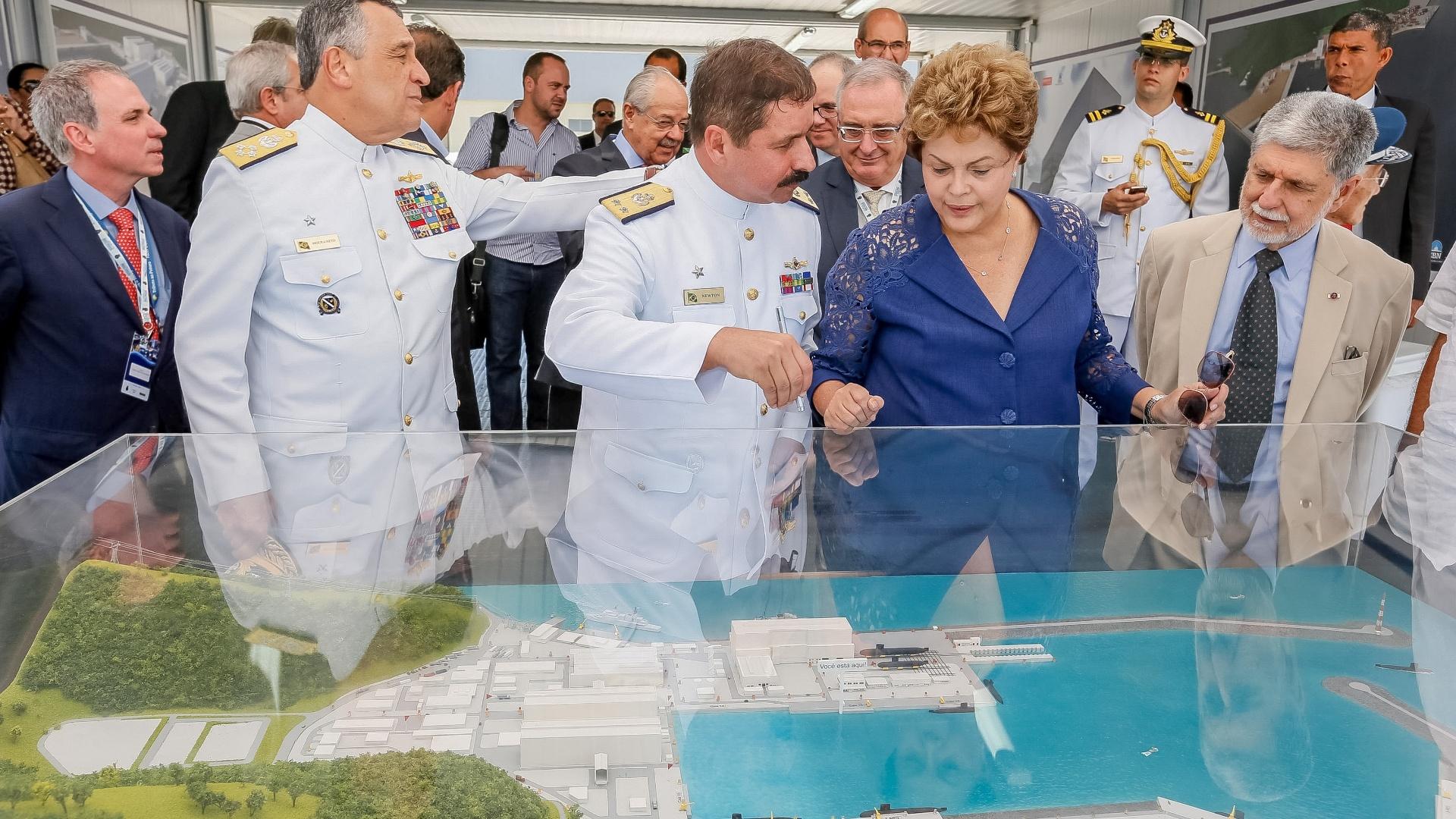 12.dez.2014 - A presidente Dilma Rousseff observa maquete, ao lado do ministro da Defesa, Celso Amorim (direita), durante a cerimônia de inauguração da primeira fase do complexo de Estaleiro e Base Naval, em Itaguaí (RJ), nesta sexta-feira (12). O estaleiro abrigará recursos técnicos e industriais que permitirão o término da fabricação de cinco submarinos (quatro convencionais e um com propulsão nuclear). Dilma defendeu o fortalecimento das Forças Armadas brasileiras.