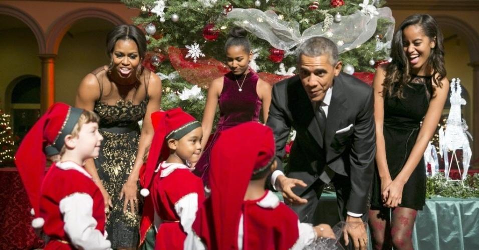 14.dez.2014 - A família Obama cumprimentou um grupo de 'duendes', neste domingo (14), antes de participar da gravação de um evento natalino da rede TNT, em Washington D.C. As crianças fantasiadas de duendes são ex-pacientes do Centro Médico Nacional para Crianças, que é o beneficiário do concerto da noite