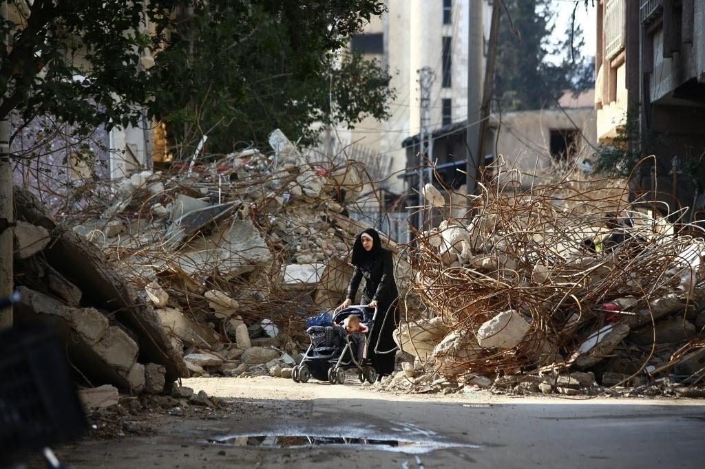12.dez.2014 - Uma mulher empurra carrinho entre os escombros dos edifícios destruídos na cidade de Douma, na Síria. O local, um subúrbio a nordeste da capital síria, tem estado cercado há mais de um ano. A imagem foi retratada no sábado (13) e divulgada nesta segunda-feira (15