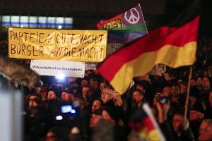 Manifestantes carregam faixas e bandeiras nacionais alemãs durante uma manifestação convocada pelo grupo anti-imigração Pegida
