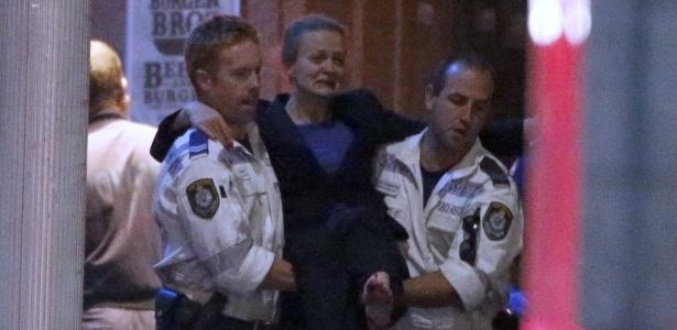 A brasileira Marcia Mikhael é carregada por policiais após tiroteio em café de Sydney; ela estava entre os reféns de um radical islâmico