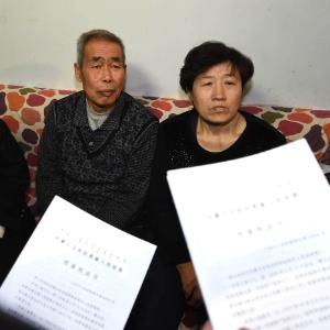 Li Sanren (à esq.) e Shang Aiyun, pais de Huugjilt, recebem documento legal sobre o novo processo nesta segunda-feira (15). O chinês foi considerado inocente 18 anos após ser sentenciado à morte, em 1996