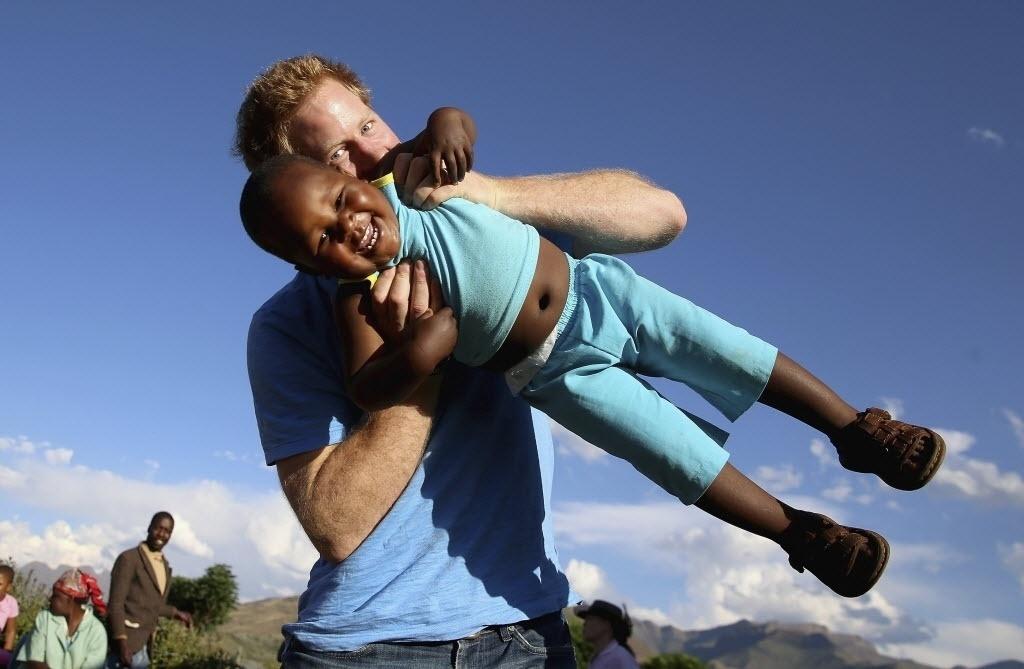 18.dez.2014 - Príncipe Harry brinca com um menino órfão de três anos durante visita a um orfanato em Maseru, no Lesoto, em foto registrada por uma menina cega, com a ajuda de um fotógrafo, no dia 6 de dezembro e divulgada nesta quinta-feira