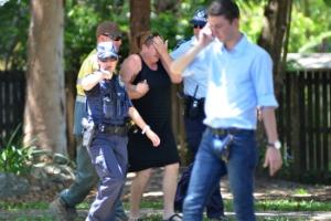 Policiais consolam mulher próximo à casa onde ocorreram as mortes