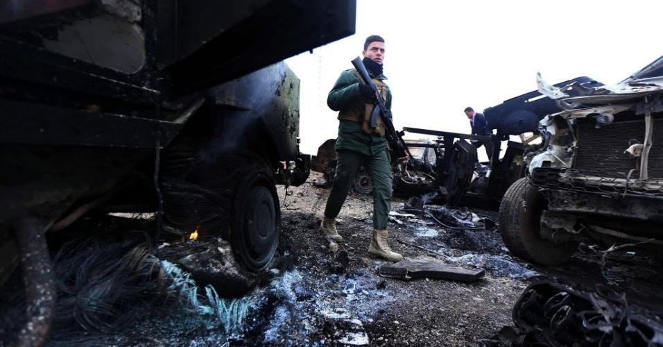 19.dez.2014 - Um combatente anda entre os veículos queimados após um ataque suicida realizado pelo grupo Estado Islâmico (EI) no vilarejo Kesarej, ao sul da cidade de Zummar, na província de Nínive, perto da fronteira com a Síria. Forças curdas apoiadas por aviões dos EUA retomaram o controle de uma grande área no Iraque