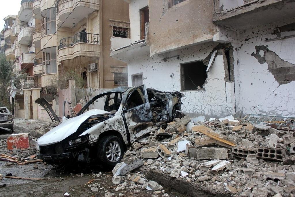 20.dez.2014 - Carro e parte de prédio ficam destruídos após um ataque aéreo feito pelo governo sírio contra a cidade de Raqa, que está sob o controle do grupo Estado Islâmico (EI). Segundo o Observatório Sírio para os Direitos Humanos, sete pessoas teriam morrido
