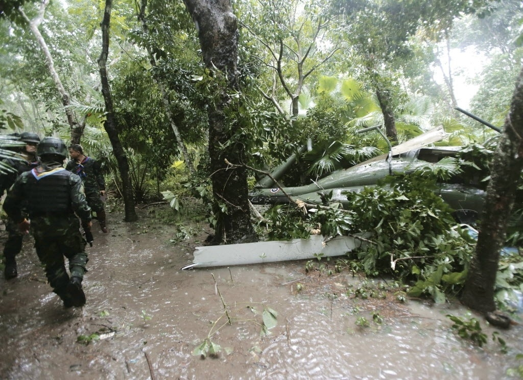 21.dez.2014 - Soldado inspeciona local da queda de um helicóptero do Exército em Yala, no sul da Tailândia, neste domingo (21). Quatro soldados tailandeses ficaram feridos no acidente durante uma missão que ajudava vítimas das enchentes na região do distrito de Muang