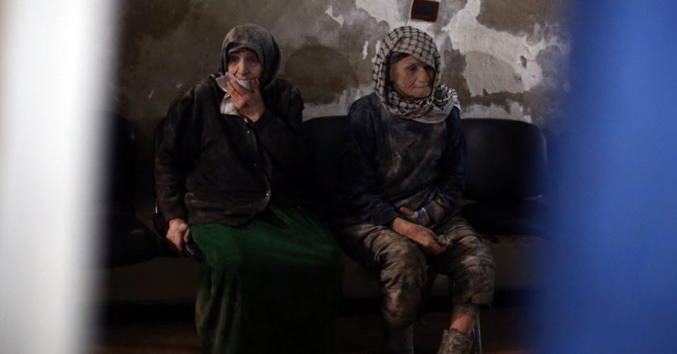 21.dez.2014 - Um casal de idosos aguarda neste domingo (21) tratamento em uma clínica improvisada na cidade rebelde sitiada de Douma, localizada a 13 km de Damasco, na Síria. O local foi atacado pelas forças do ditador sírio, Bashar Assad