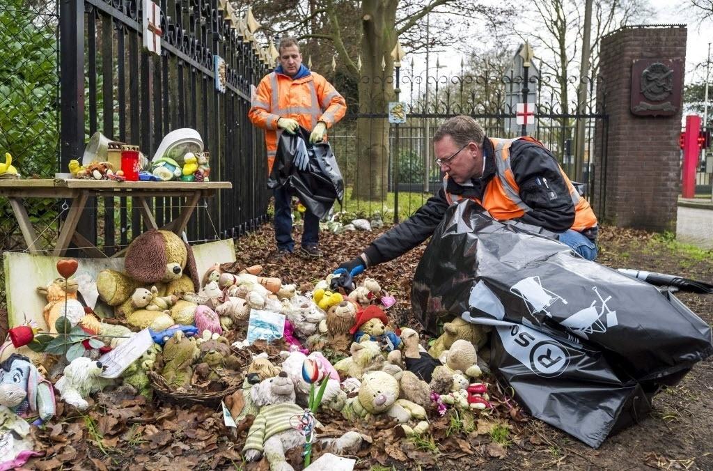 22.dez.2014 - Agentes de limpeza removem nesta segunda-feira (22) objetos colocados em homenagem às vítimas do voo MH17, da Malaysia Ailines, que caiu na Ucrânia no mês de julho, na entrada do local onde autoridades identificam os restos mortais, em Hilversum, na Holanda