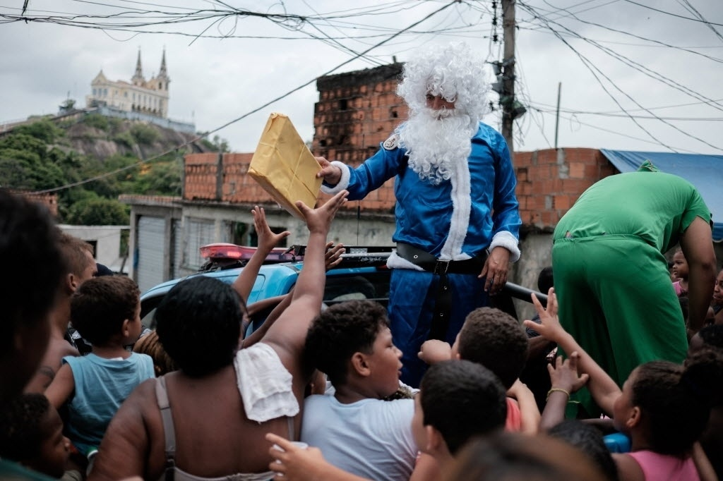24.dez.2014 - Comandante de UPP (Unidades de Polícia Pacificadora) da favela Vila Cruzeiro, na zona norte do Rio de Janeiro, se veste de Papai Noel e entrega presentes de Natal para crianças