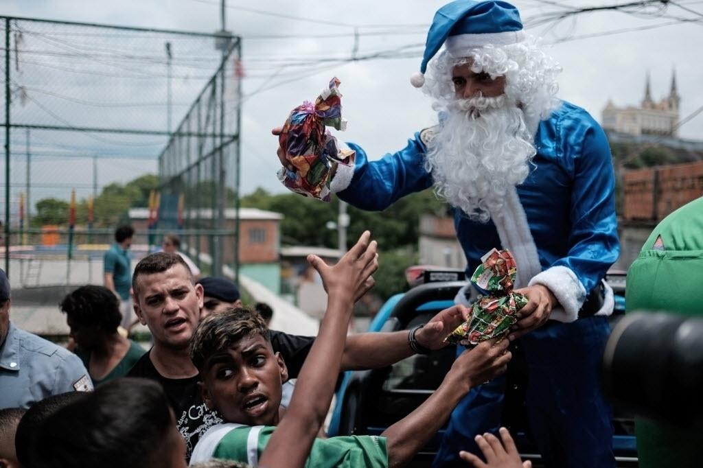24.dez.2014 - Comandante de UPP (Unidades de Polícia Pacificadora) da favela Vila Cruzeiro, na zona norte do Rio de Janeiro, se veste de Papai Noel e entrega presentes de Natal para moradores da comunidade