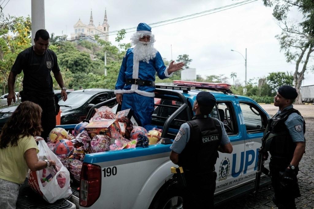 24.dez.2014 - Comandante e policiais da UPP (Unidades de Polícia Pacificadora) da favela Vila Cruzeiro, na zona norte do Rio de Janeiro, separa presentes de Natal para entregas às crianças do local