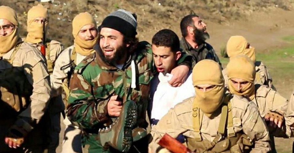 24.dez.2014 - Imagem divulgada pelo grupo Estado Islâmico (EI) em sites jihadistas mostram supostamente um piloto Jordanian (de roupa branca) capturado pelos combatentes que teriam derrubado um avião militar da coalizão internacional na cidade de Al Raqqah, na Síria