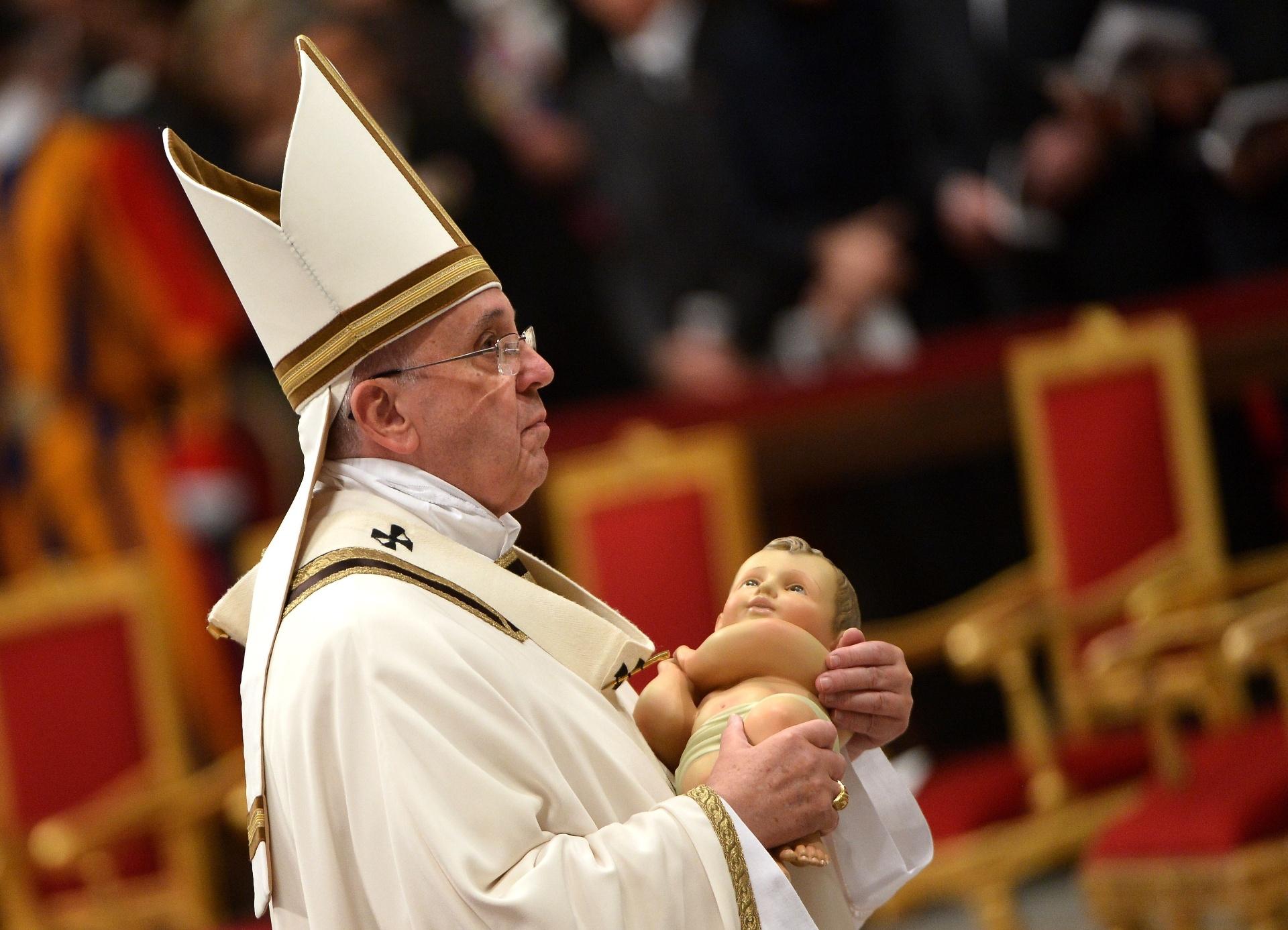 24.dez.2014 - O Papa Francisco carrega a imagem do menino Jesus durante a celebração da Missa do Galo, na Basílica de São Pedro, no Vaticano, que lembra o nascimento de Jesus Cristo
