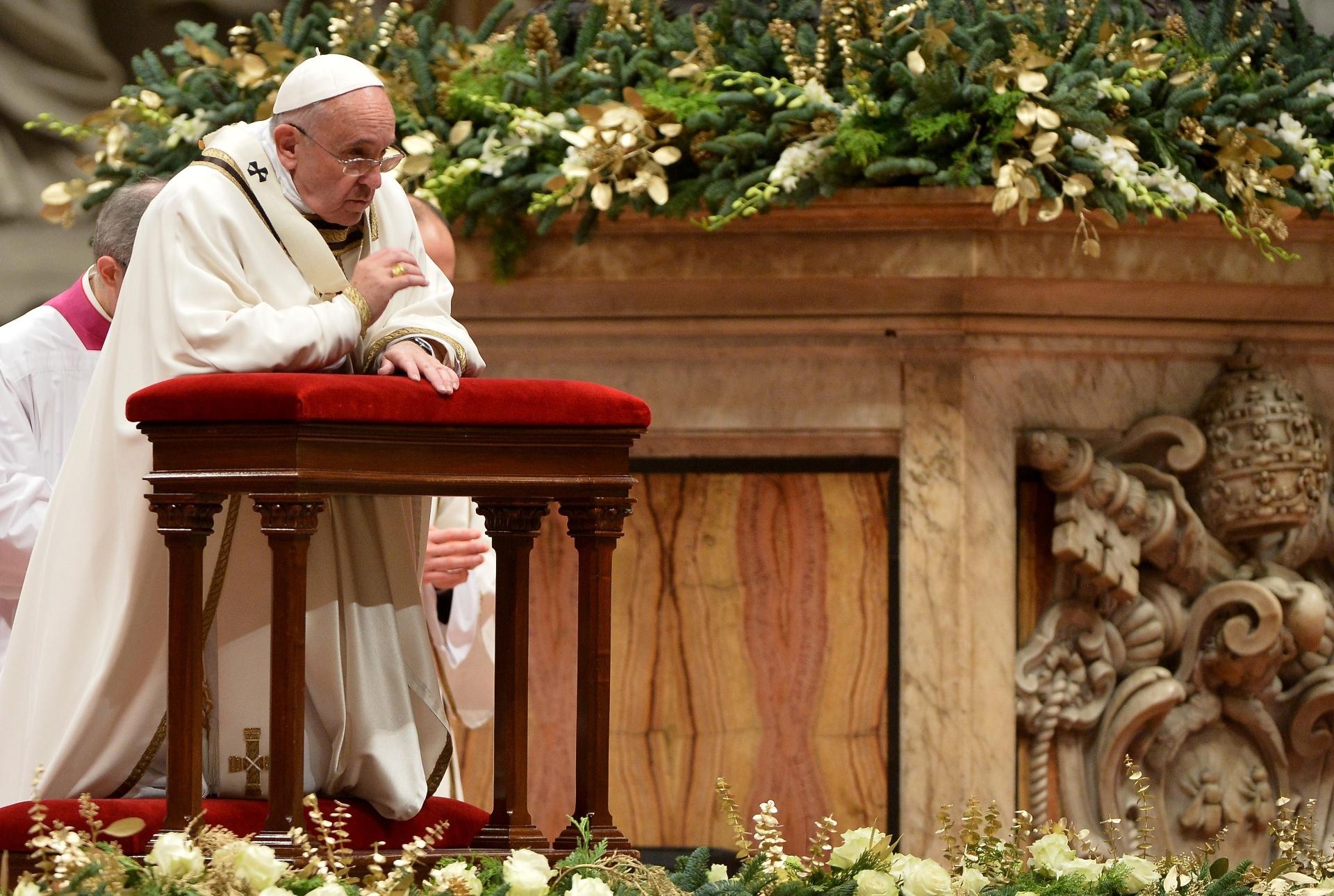 24.dez.2014 - O Papa Francisco se ajoelha para rezar durante da celebração a Missa do Galo, na Basílica de São Pedro, no Vaticano, que lembra o nascimento de Jesus Cristo