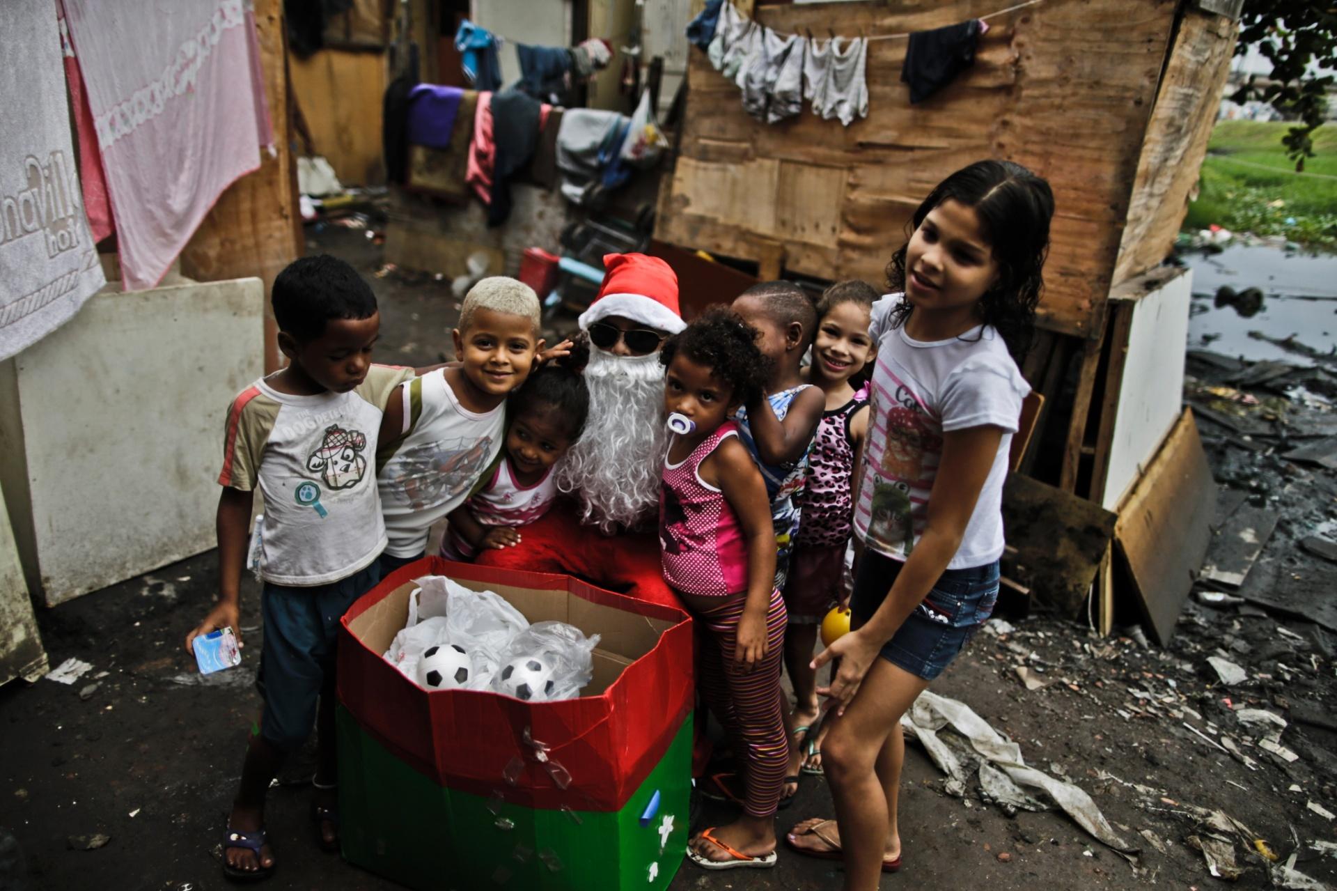24.dez.2014 - Papai Noel tira foto com crianças após distribuir presentes na comunidade da McLaren, no conjunto de favelas da Maré, na zona norte do Rio de Janeiro