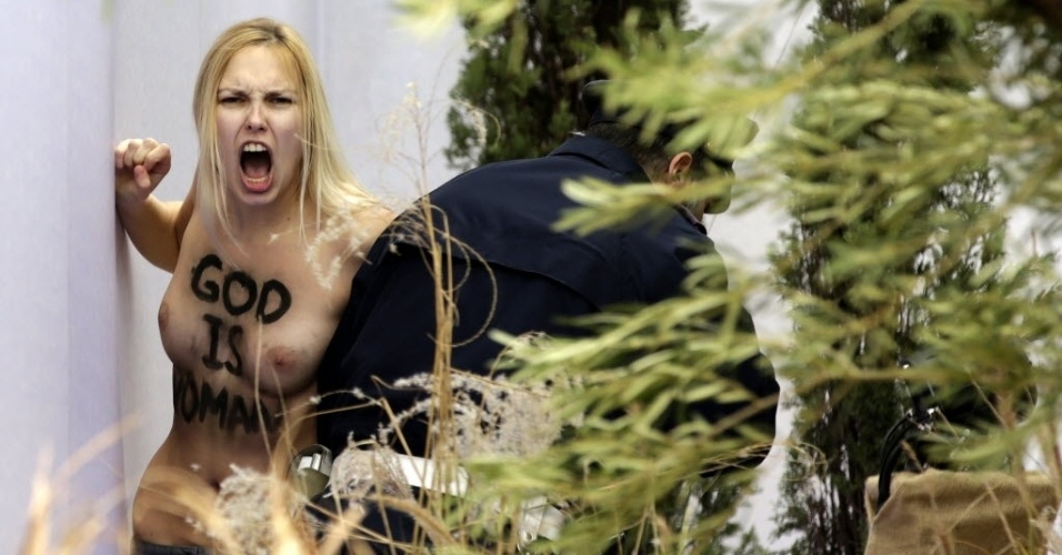 25.dez.2014 - Uma ativista do Femen é presa pela polícia do Vaticano nesta quinta-feira (25) ao protestar dentro do presépio da praça São Pedro com os seios à mostra e a frase