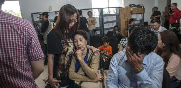 Familiares dos passageiros do voo 8501 da AirAsia aguardam informações no aeroporto de Surabaia, na Indonésia, de onde a aeronave partiu em direção a Cingapura