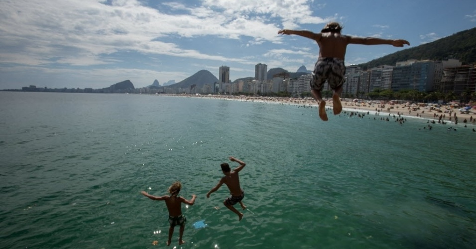 30.dez.2014 - Criancas se divertem saltando da pedra do Leme, na zona sul do Rio de Janeiro, no penúltimo dia de 2014. Com o forte calor que faz na capital fluminense, a praia é a opcão de lazer mais procurada