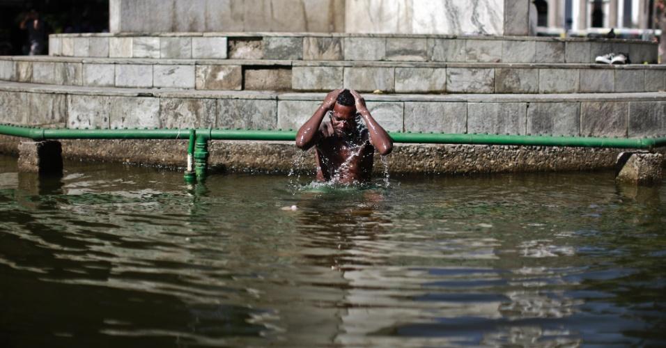 2.jan.2015 - Morador de rua se refresca no chafariz do largo do Machado, nesta sexta-feira (2), em dia de forte calor no Rio de Janeiro. Termômetros da cidade registraram temperaturas superior a 40º C , com sensação térmica de 45º C