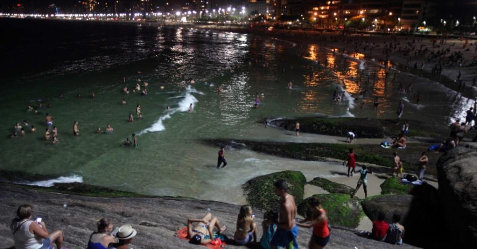 3.jan.2015 - Na noite deste sábado (3), a praia do Arpoador, no Rio de Janeiro, permanece cheia de banhistas. O calor na cidade caiu no primeiro fim-de-semana do ano, e ficou em torno de 30ºC. No entanto as águas tranquilas na praia levam turistas a aproveitar o mar até tarde