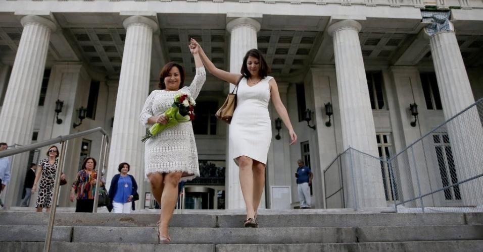 5.jan.2015 - As recém-casadas Karla Arguello (esquerda) e Catherina Pareto saem do tribunal de Miami-Dade, nesta segunda-feira (5), como o primeiro casal a se casar na Flórida. O casamento gay agora é permitido em todo Estado depois da Justiça considerar que a proibição do casamento gay é inconstitucional