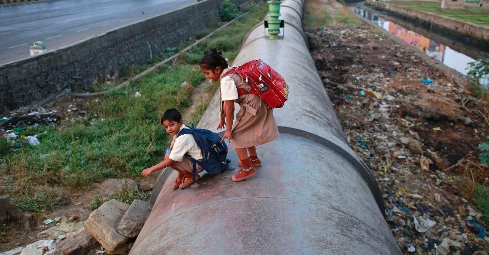 5.jan.2015 - Crianças passam por uma adutora no caminha para a escola na Índia