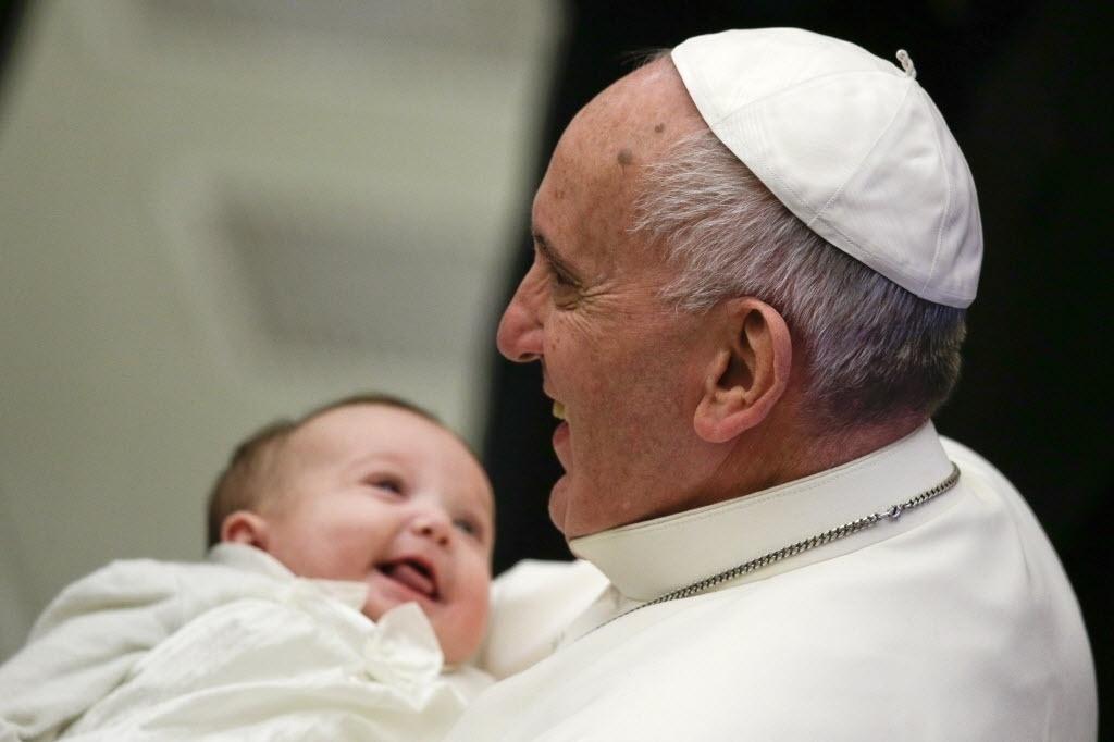 7.jan.2015 - Papa Francisco segura um bebê sorridente durante sua audiência geral semanal no Vaticano