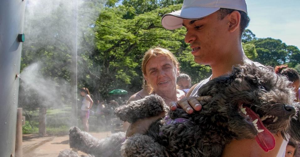 10.jan.2015 - Em um sábado de calor, com temperatura máxima prevista de 35ºC, paulistano ajuda cachorro a se refrescar durante passeio no parque do Ibirapuera, em São Paulo. Há previsão de chuva entre o final da tarde e o início da noite deste sábado (10) devido ao calor e à entrada de brisa marítima