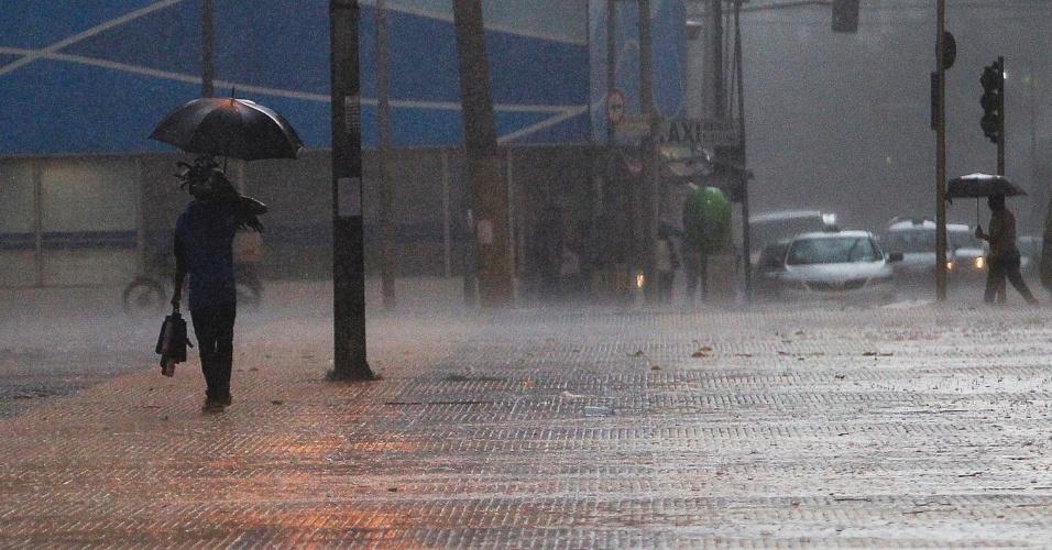 12.jan.2015 - Vendedor de guarda-chuvas caminha na Praça da República, no centro de São Paulo, durante tempestade que atinge a capital paulista nesta segunda-feira (12). Com as chuvas, toda a cidade recebeu estado de atenção às 16h05