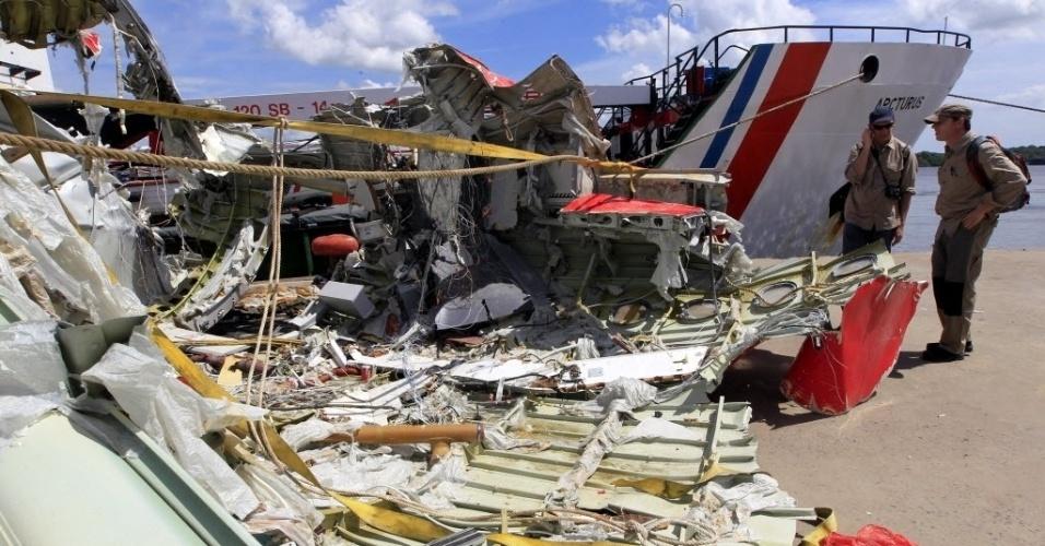 12.jan.2015 - Dois pesquisadores analisam os destroços recuperados do avião da AirAsia que caiu há duas semanas no mar de Java, com 162 pessoas a bordo. De acordo com uma fonte próxima às investigações, dados do radar da aeronave aparentemente mostram que o avião fez uma subida brusca para evitar as tempestades que assolavam a região e ficou num ângulo