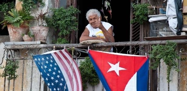 Cubano acena de sua varanda decorada com bandeiras dos EUA e de Cuba, em Havana