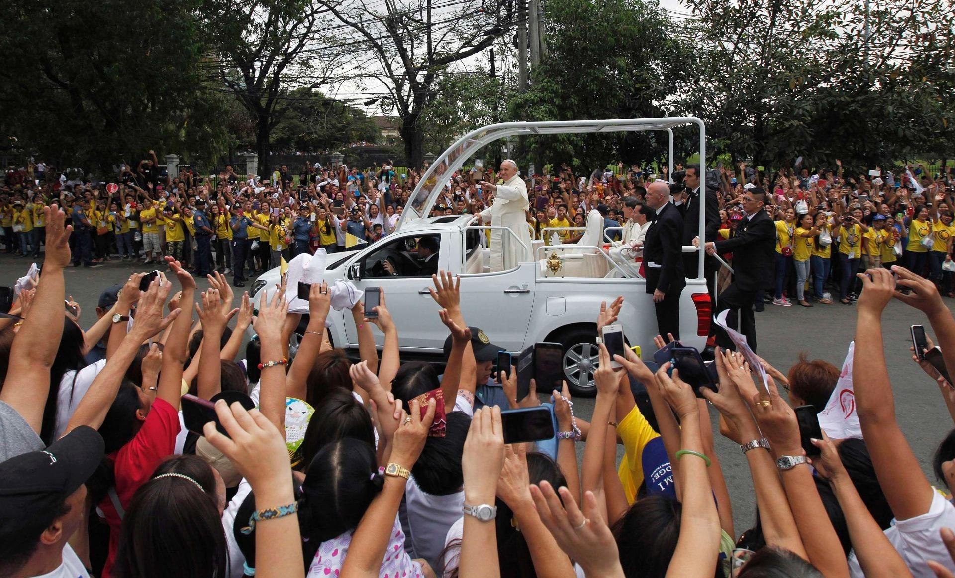 16.jan.2015 - Papa Francisco acena para multidão que saiu às ruas de Manila para poder ver a sua passagem. Em um evento que não estava programado após a missa na catedral da Imaculada Conceição, na capital filipina, o pontífice foi até a sede de uma associação para se reunir com cerca de 300 crianças que foram resgatadas das ruas