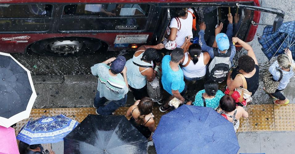 16.jan.2015 - Paulistanos se aglomeram em porta de ônibus para fugir da chuva nesta sexta-feira (16) em ponto da avenida Brigadeiro Faria Lima, no bairro de Pinheiros, em São Paulo