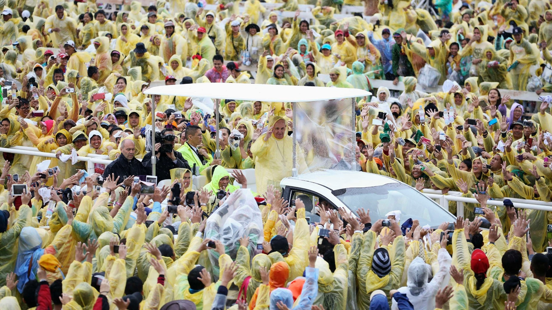 17.jan.2015 - Usando uma proteção para chuva, papa Francisco acena para multidão antes de celebrar uma missa em Tacloban, devastada pelo tufão Haiyan em 2013, na maior tormenta já enfrentada pelas Filipinas e que deixou milhares de mortos. A tempestade tropical Mekkhala está se aproximando da região, o que deixa o país em alerta