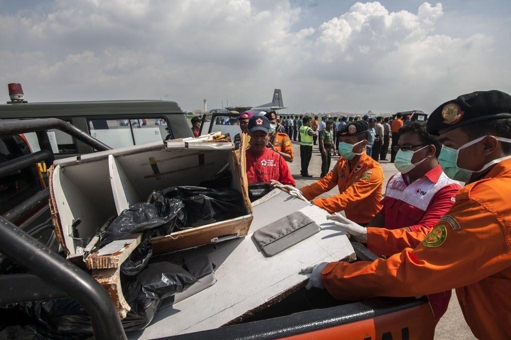 17.jan.2015 - Integrantes da agência de operações de busca e resgate da Indonésia examinam neste sábado (17) parte dos destroços do avião da AirAsia, que caiu em 28 de dezembro no mar de Java com 162 pessoas a bordo, em Surabaya, leste da ilha de Java. A fuselagem da aeronave será retirada do mar